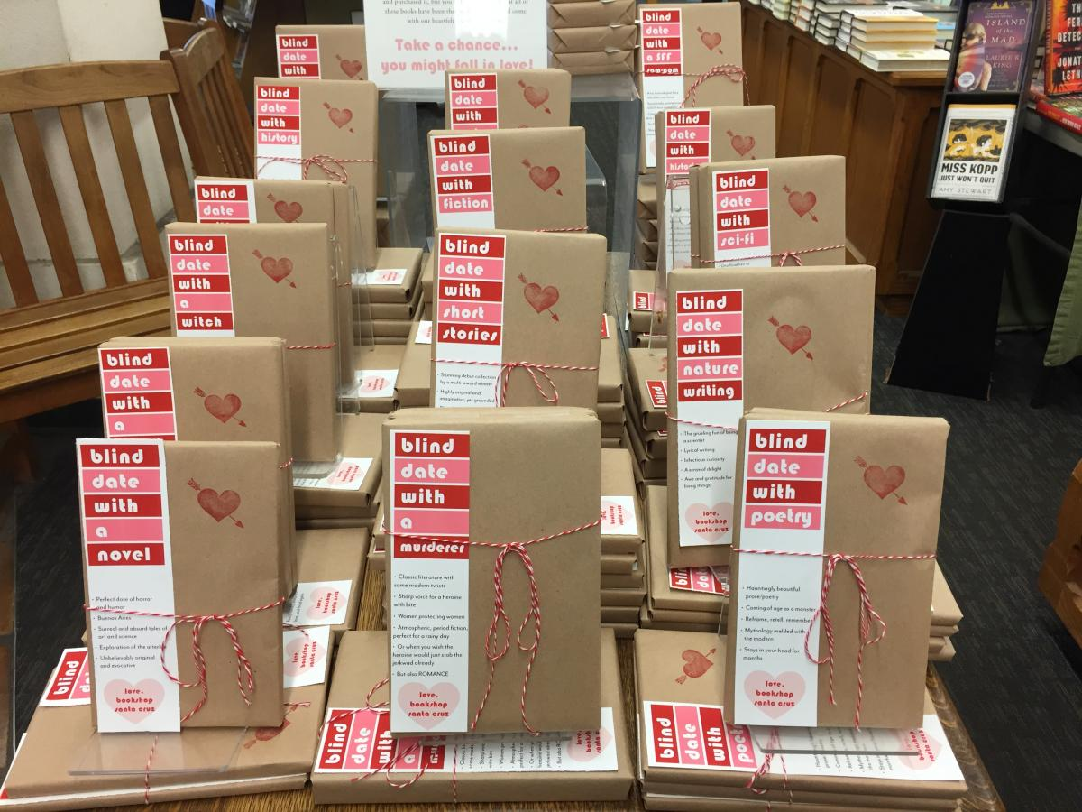 "A table with piles of books wrapped in brown paper and string, with white, red, and pink book marks that say ""Blind Date with ....."""