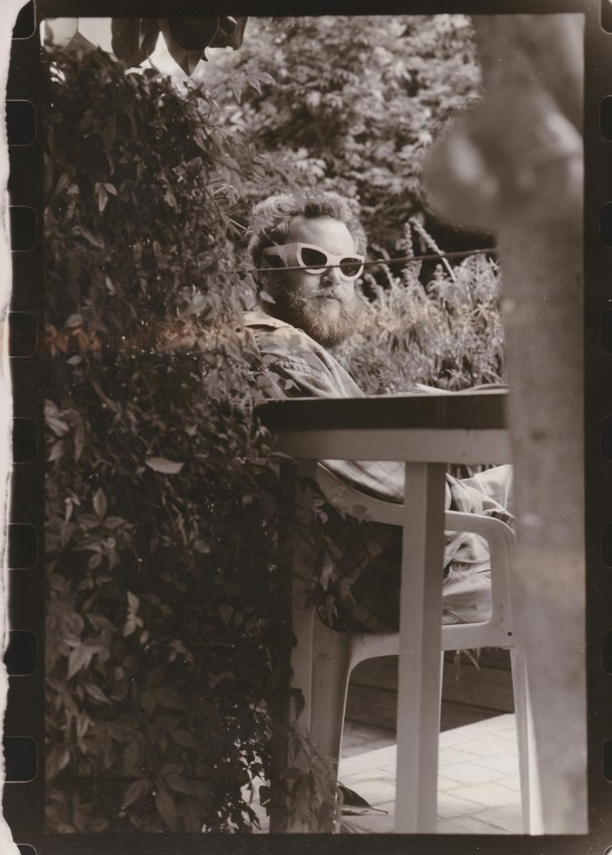 "A black and white photo of a seated man wearing ""alien eyes"" sunglasses, looking backwards towards the camera amongst foliage."