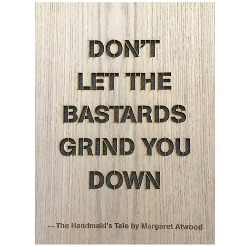 "A wooden rectangle with the words laser-cut in ""Don't let the bastards grind you down."""
