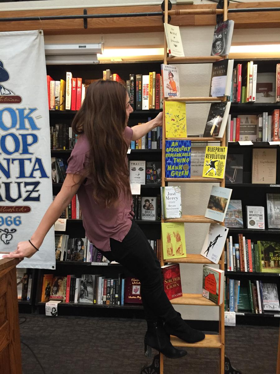A young woman with long, loose brown hair perches out from a wooden ladder placed against a wall of bookshelves, looking with a smile at the ladder, where two books rest cover-out on each rung.