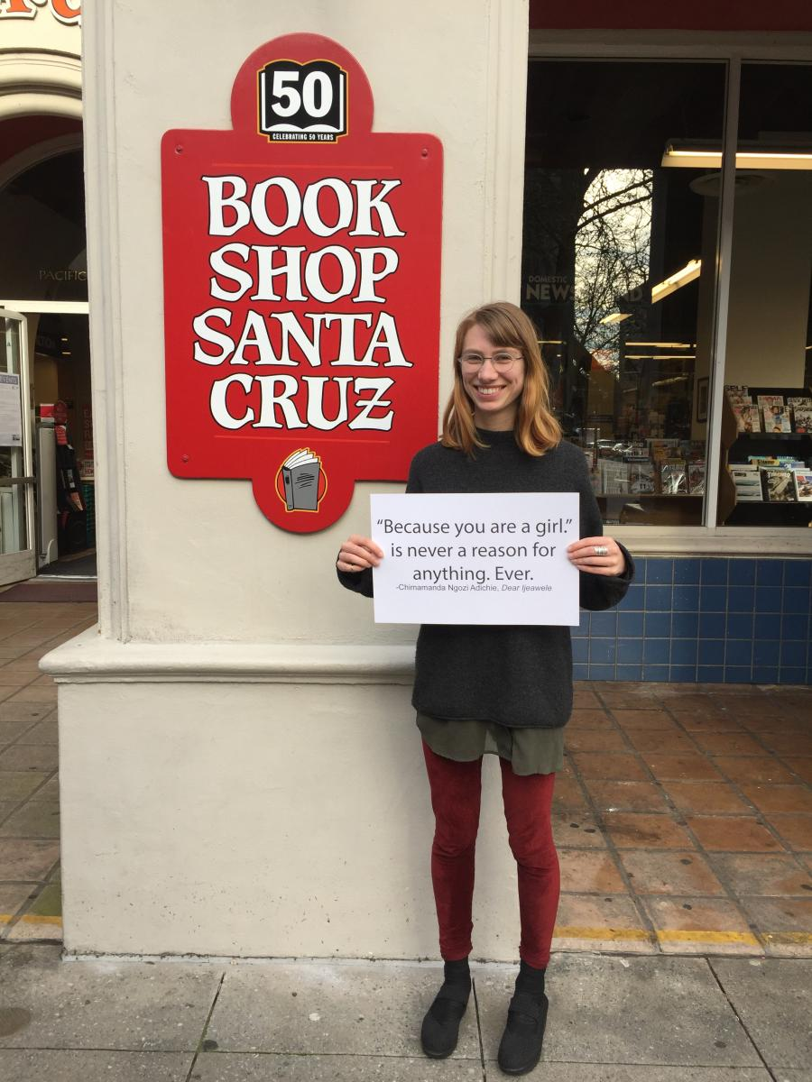 "A young woman stands in front of the Bookshop Santa Cruz sign with a paper with the quote ""Because you are a girl is never a reason for anything. Ever."""