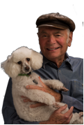 A smiling white man wearing a leather cap, and holding a poodle, looking forward.