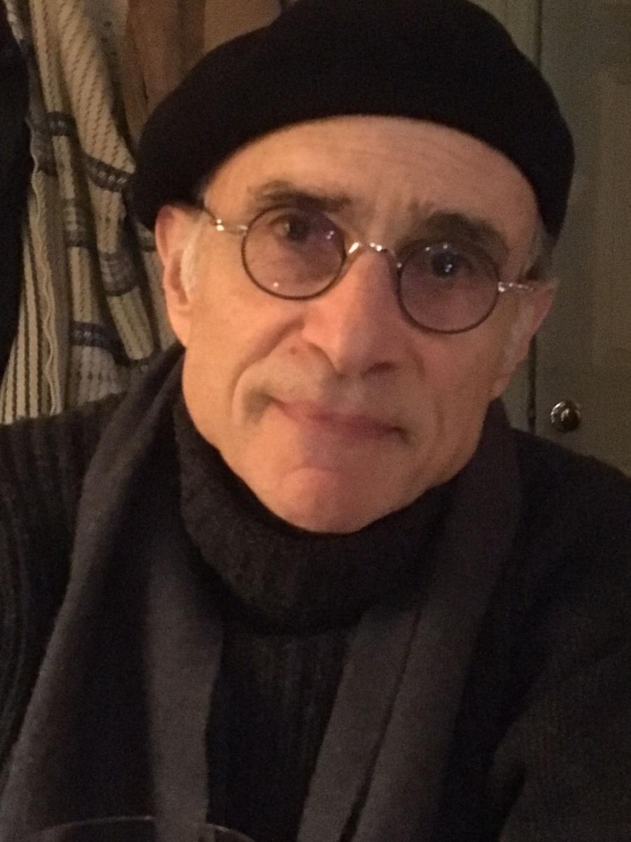 A man looking straight forward, wearing glasses, a black beret, and a scarf.