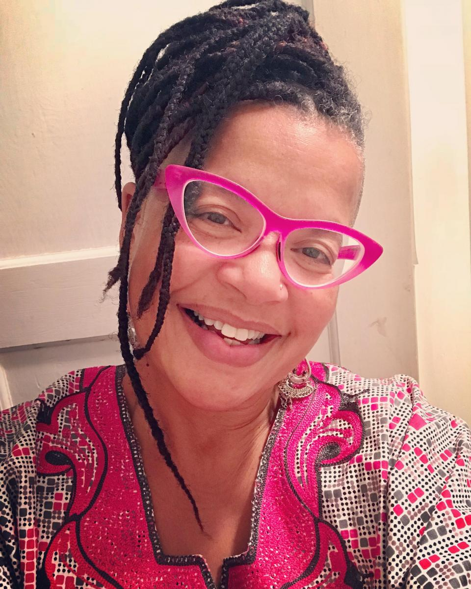 The face and shoulders of a black woman with hair up in braids, wearing pink cat-eye glasses and smiling.