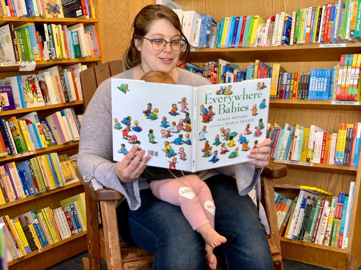 A woman sitting in a rocking chair with a baby on her lap, reading the picture book, Everywhere Babies.