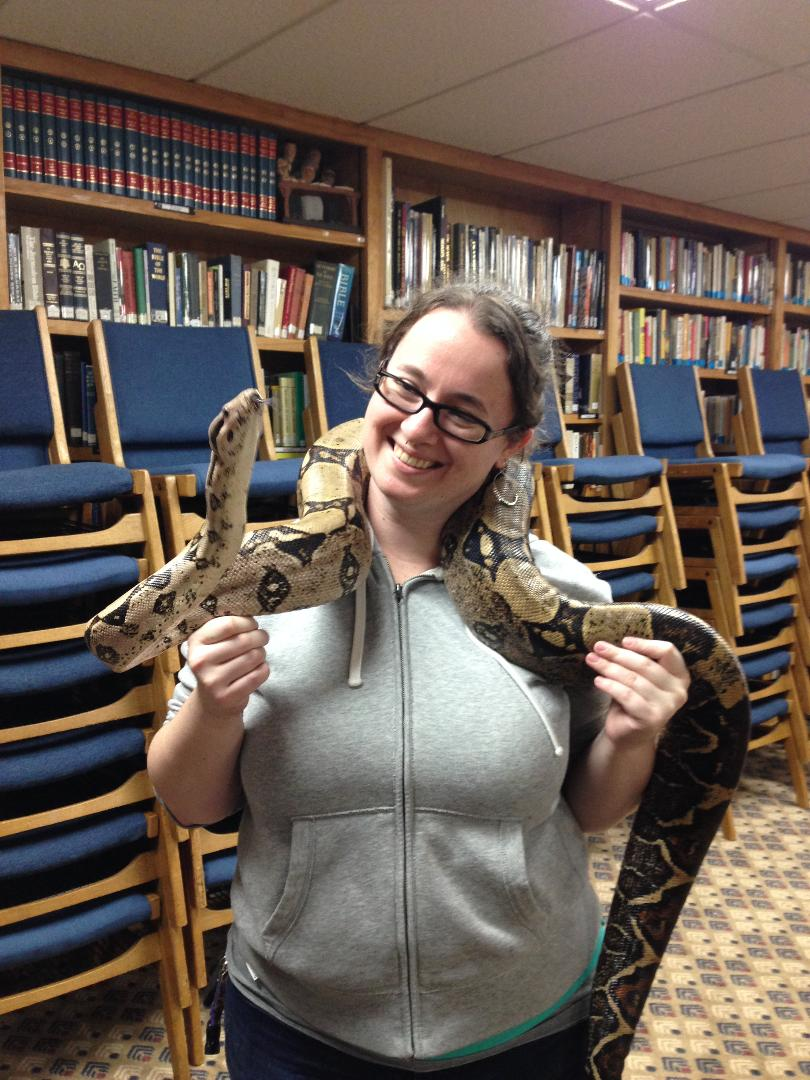 A caucasian woman wearing glasses, holding a large snake around her shoulder in front of stacks of chairs and books.