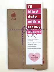 A book wrapped in brown paper, with a white, red, and pink bookmark that says YA Blind Date with a Fantasy Spy Queen