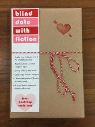 "A book wrapped in brown paper and tied with red and white string. It has a red heart stamp, and a bookmark that reads ""blind date with fiction"""