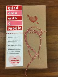 "A book wrapped in brown paper and tied with red and white string. It has a red heart stamp, and a bookmark that reads ""blind date with a foodie"""