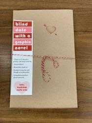 "A book wrapped in brown paper and tied with red and white string. It has a red heart stamp, and a bookmark that reads ""blind date with a graphic novel"""