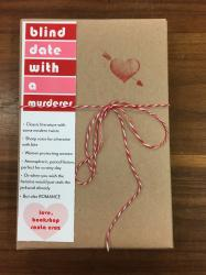 "A book wrapped in brown paper and tied with red and white string. It has a red heart stamp, and a bookmark that reads ""blind date with a murderer"""