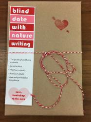 "A book wrapped in brown paper and tied with red and white string. It has a red heart stamp, and a bookmark that reads ""blind date with nature writing"""