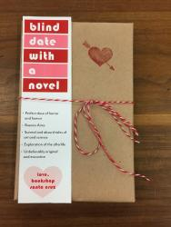 "A book wrapped in brown paper, with a red stamp heart, tied with red and white string, with a bookmark on the front that says ""blind date with a novel"""
