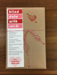 "A book wrapped in brown paper and tied with red and white string. It has a red heart stamp, and a bookmark that reads ""blind date with sci-fi"""
