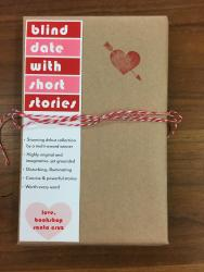 "A book wrapped in brown paper and tied with red and white string. It has a red heart stamp, and a bookmark that reads ""blind date with short stories""."