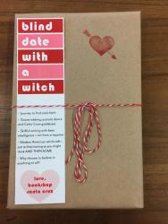 "A book wrapped in brown paper and tied with red and white string. It has a red heart stamp, and a bookmark that reads ""blind date with a witch"""
