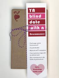 A book wrapped in brown paper, with a white, red, and pink bookmark that says YA Blind Date with a Necromancer