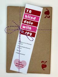 A book wrapped in brown paper, with a white, red, and pink bookmark that says YA Blind Date with a Spy